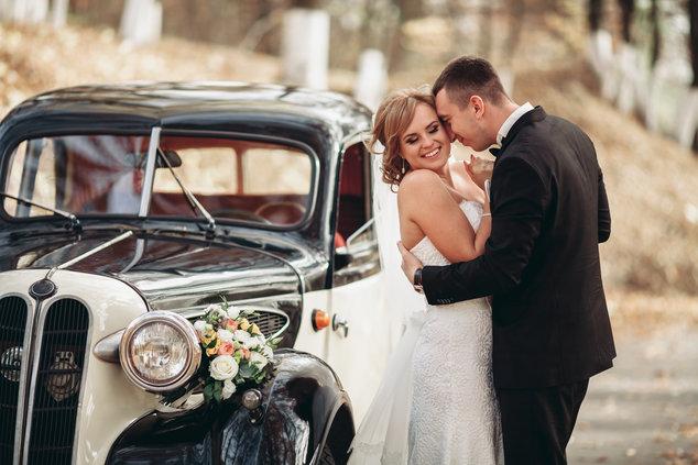 Jonggehuwden naast huwelijksauto